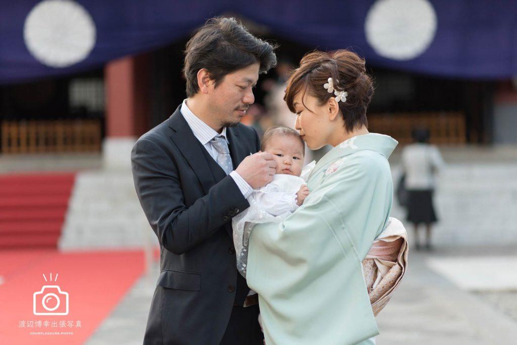 赤坂日枝神社の本殿の前で赤ちゃんを抱き頭にキスをする女性