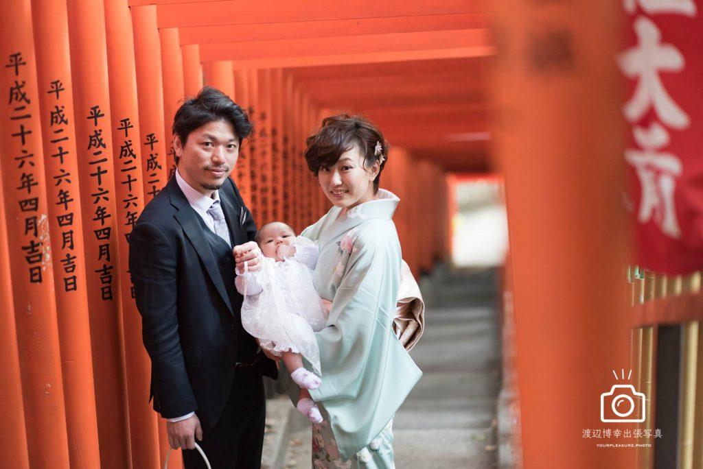 赤坂日枝神社の千本鳥居の下で立つ赤ちゃんを抱いた和装の女性と横に立つ男性