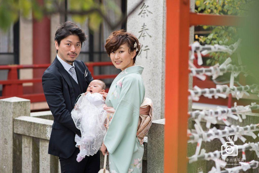 赤ちゃんを男性と横に立つ和装の女性