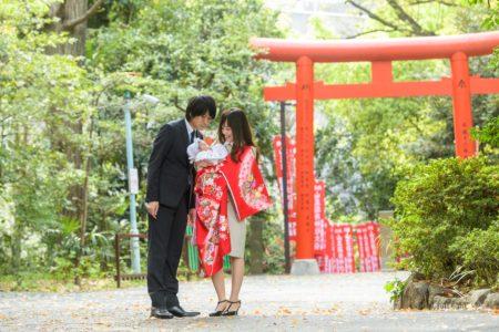 赤坂の日枝神社でお宮参りの掛着を着て赤ちゃんを抱く夫婦の写真