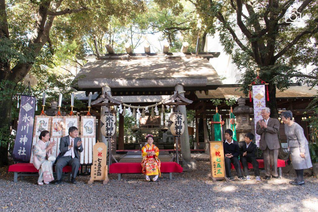 川越氷川神社で七五三のオレンジの着物を着た女の子に拍手を送る家族