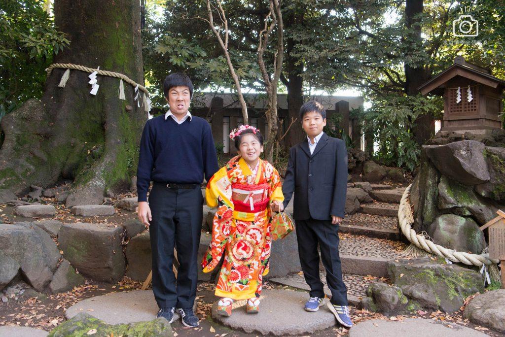 七五三のオレンジ色の着物を着た女の子と両脇に立つ男の子
