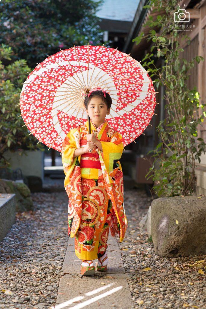 赤い和傘をさし立つオレンジの着物を着た女の子