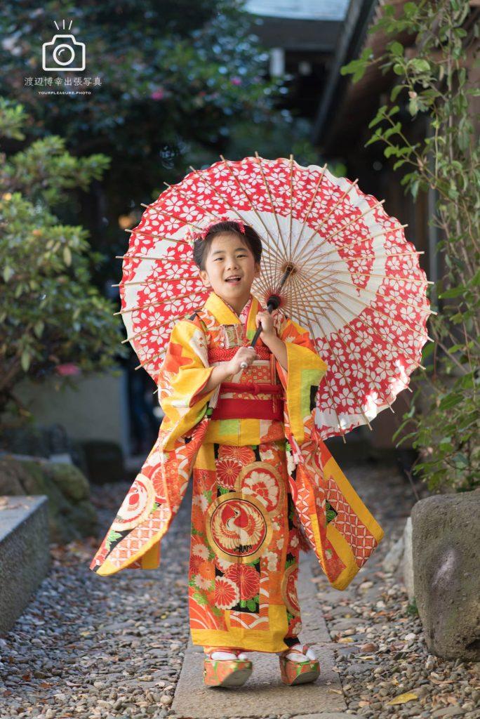 赤い和傘をさして立つオレンジの着物を着た女の子