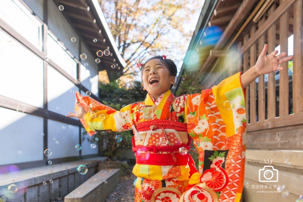 オレンジの着物を着た女の子が笑いながら手を広げている