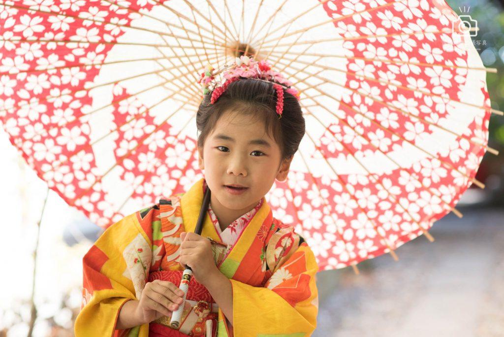 和傘をさしこちらを見て微笑むオレンジ色の着物を着た女の子