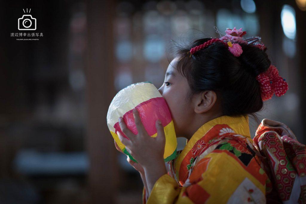 紙風船を膨らませている女の子の横顔