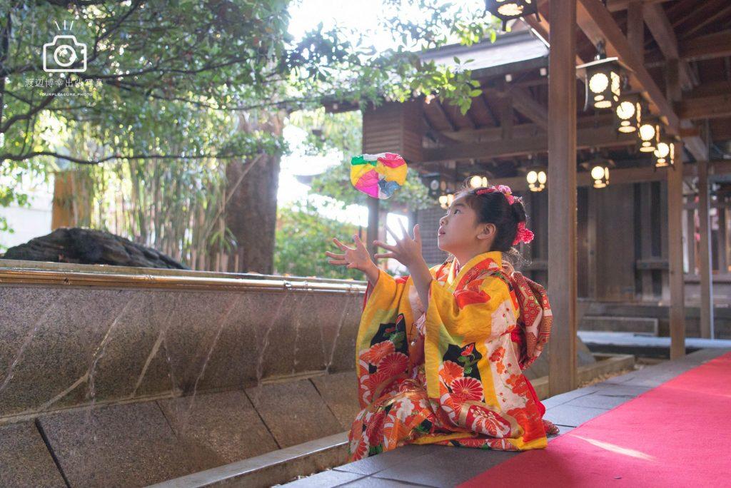 オレンジの着物を着た女の子が座りながら紙風船で遊んでいる