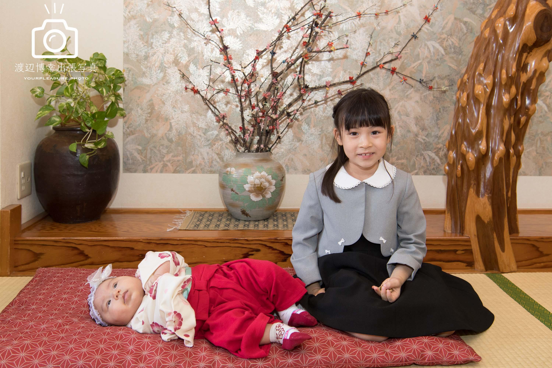 座敷に寝転ぶ赤ちゃんと女の子