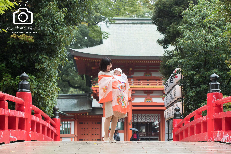 大宮氷川神社の赤い橋の上に赤ちゃんを抱っこして掛着姿で立つママ