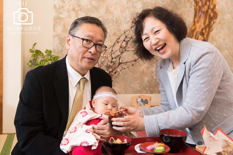お食い初めをする赤ちゃんとご祖父母