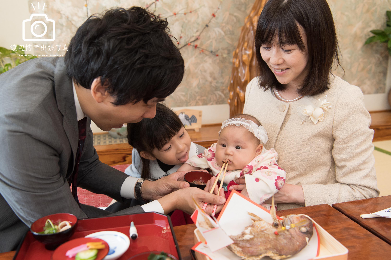 お食い初めをする赤ちゃんと家族