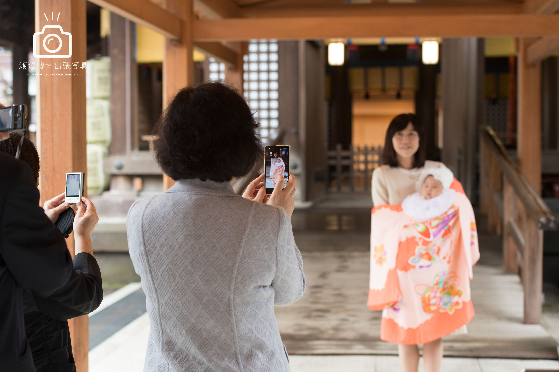 赤ちゃんを抱っこした掛着姿の母親をスマホで撮影している