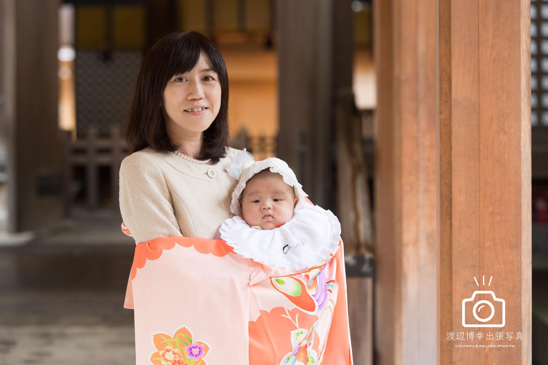 お宮参りの掛着を着て赤ちゃんを抱っこする母親