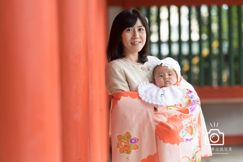 大宮氷川神社の回廊の赤い柱のそばに立つ赤ちゃんを抱っこした掛着姿のママ