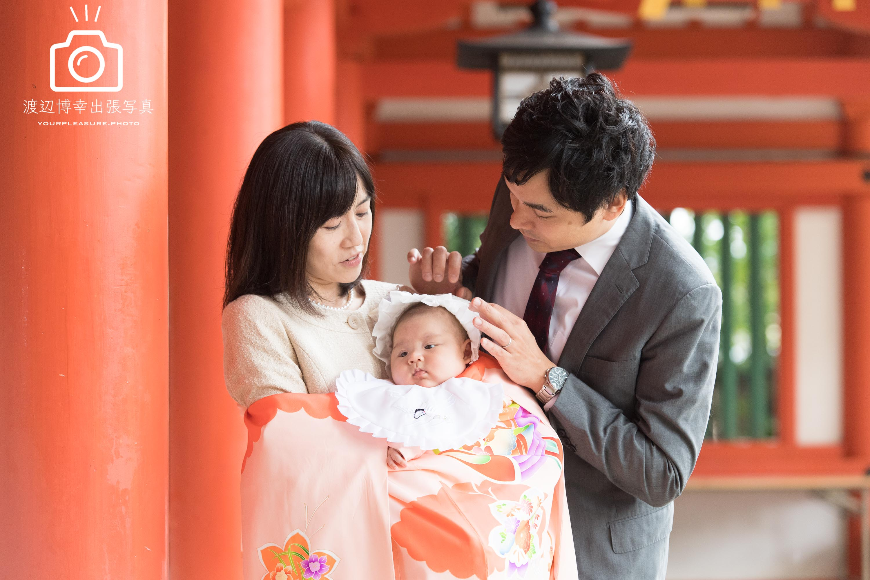 大宮氷川神社の回廊の赤い柱のそばに立つ赤ちゃんを抱っこした掛着姿のママとパパ