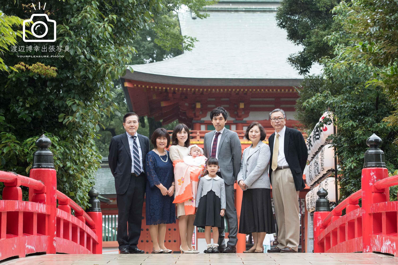 大宮氷川神社の赤い橋の上に立つ家族