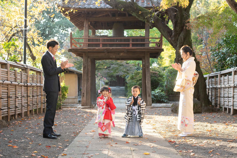 神社の鳥居の前で立つ七五三の女の子と男の子に拍手をするパパとママ