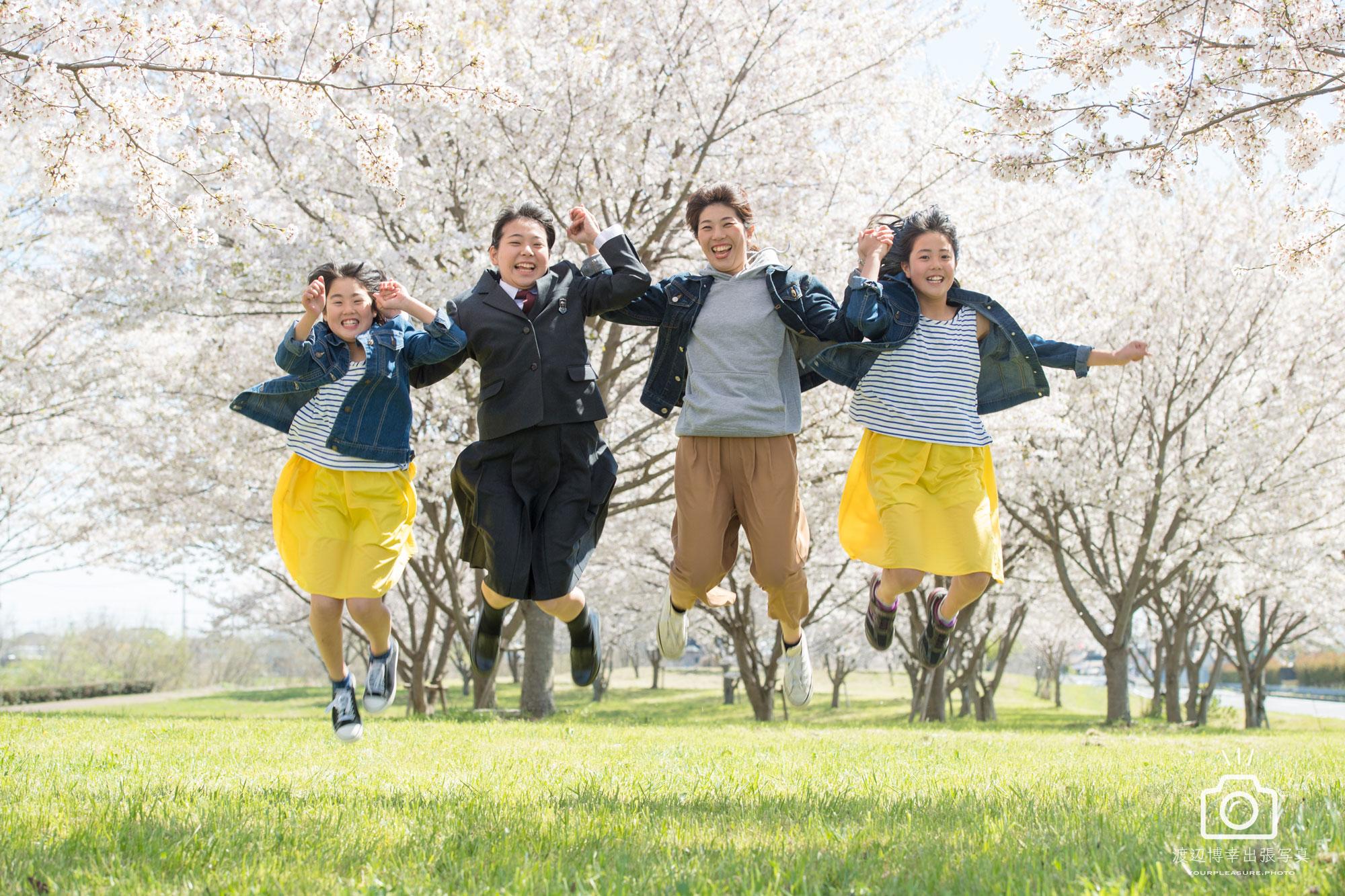 桜の中、家族4人でジャンプしている