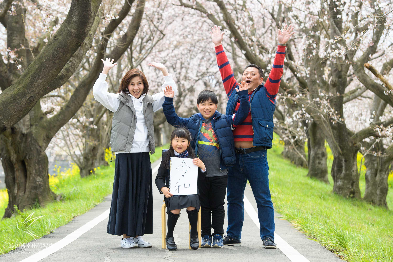 桜並木の下でバンザイをする家族