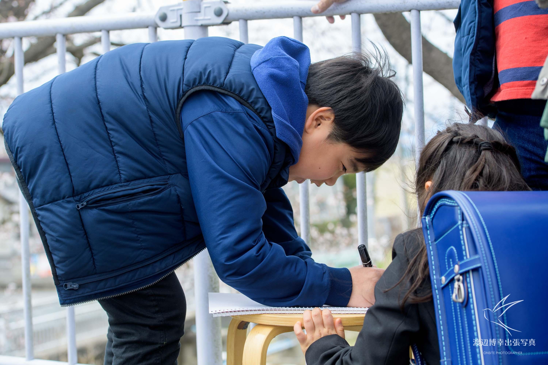 画用紙に文字を書いている少年