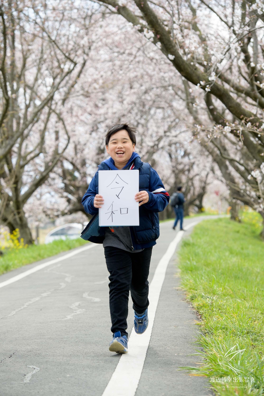 令和と書かれた画用紙をもって走る少年