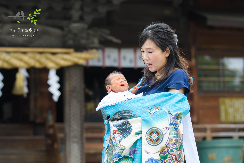 神社本殿前で掛着姿で赤ちゃんを抱く女性