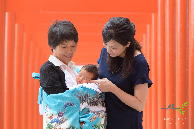 赤い鳥居の下で掛着姿で赤ちゃんを抱く祖母と横に立つ母親