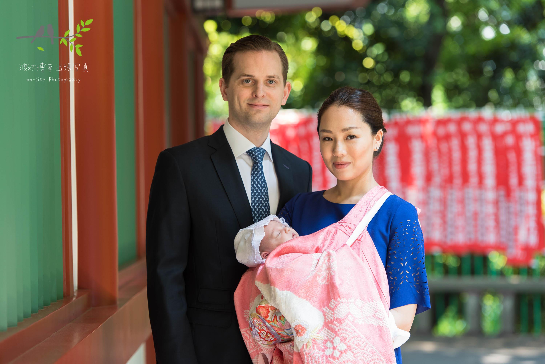 掛着を着た母親に抱かれる赤ちゃんと横に立つ父親