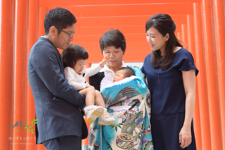赤い鳥居の下で掛着姿で赤ちゃんを抱く祖母と横に立つ母親と家族