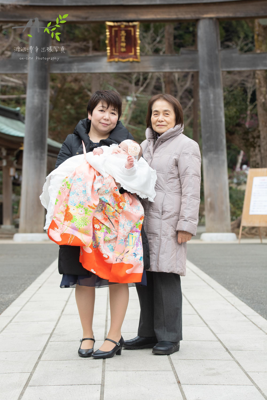神社の鳥居の前に立つ掛着姿の母と祖母と赤ちゃん