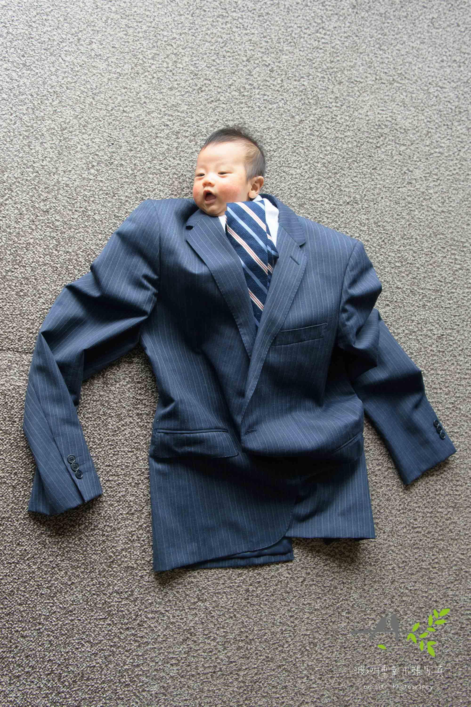 大人用のスーツを着る赤ちゃん