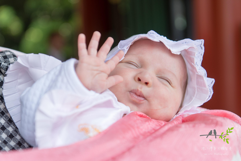 抱っこされ片手を上げた赤ちゃん