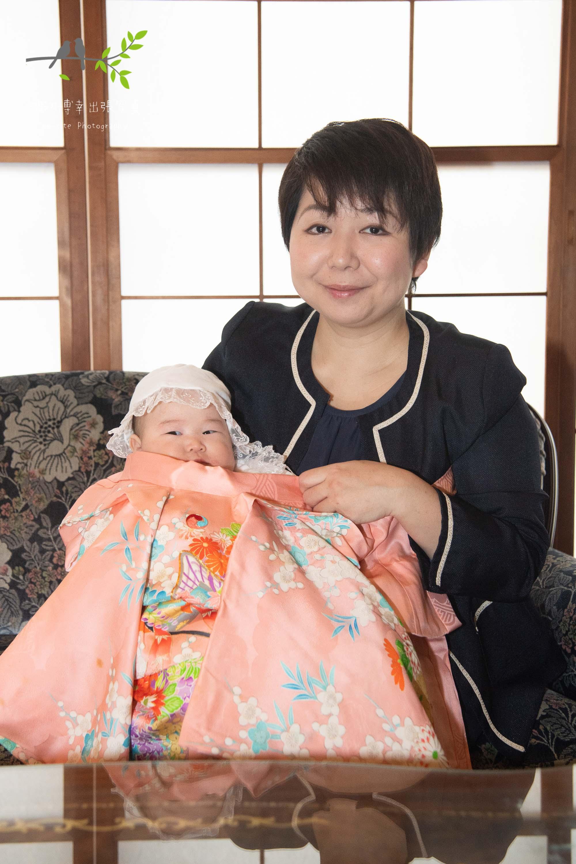 母に抱かれた掛着を着た赤ちゃん