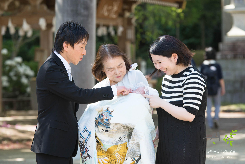 赤ちゃんのほっぺたを触る家族