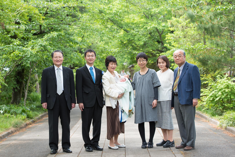 赤ちゃんを抱き神社の参道に立つ大人6人