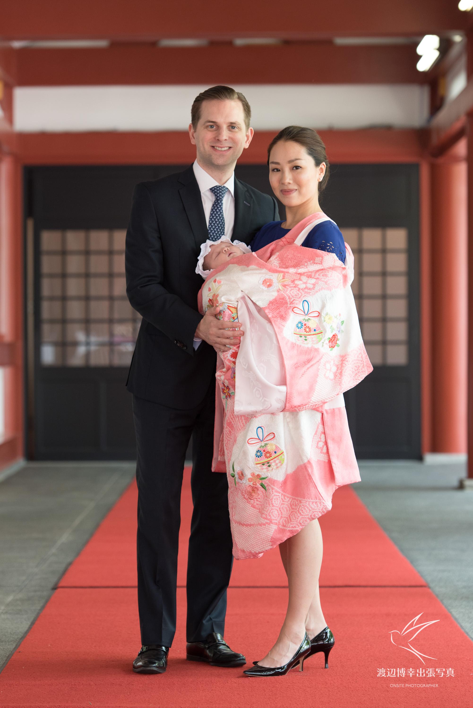 赤ちゃんを抱いたお宮参りの掛着姿の和装の女性と横に立つ男性
