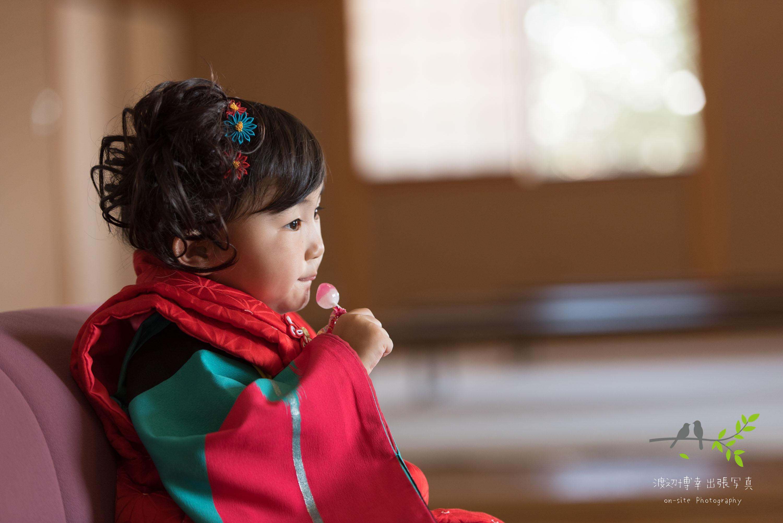 着物を着て椅子に座りチュッパチャップスを持つ女の子