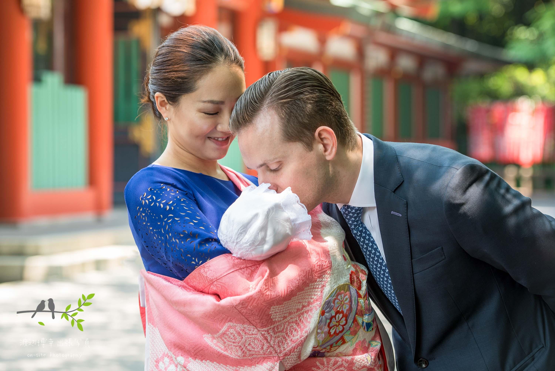 掛着を着た母親に抱かれる赤ちゃんにキスをする父親