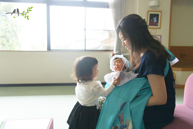 赤ちゃんを抱く女性に寄り添う女の子