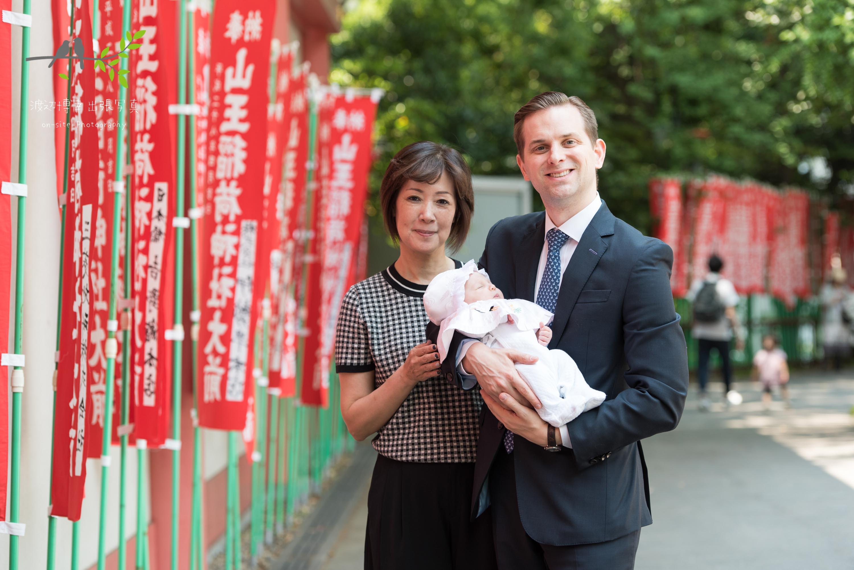 赤く連続したのぼり旗の横で赤ちゃんを抱く女性と男性