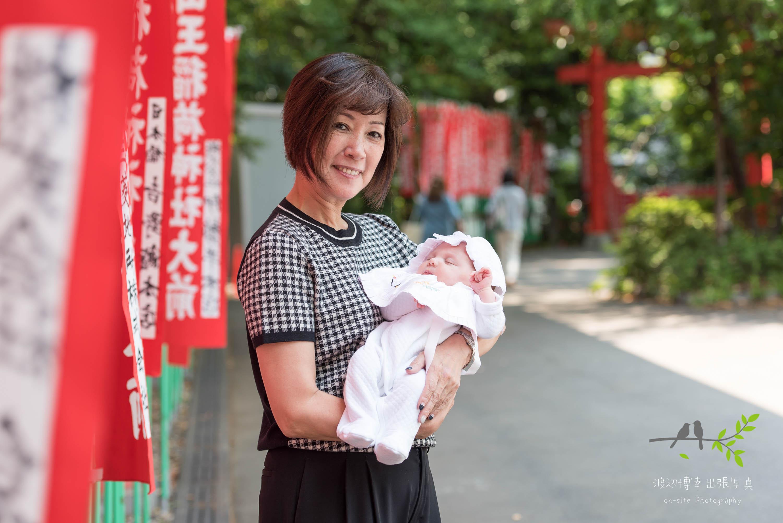 赤く連続したのぼり旗の横で赤ちゃんを抱く女性
