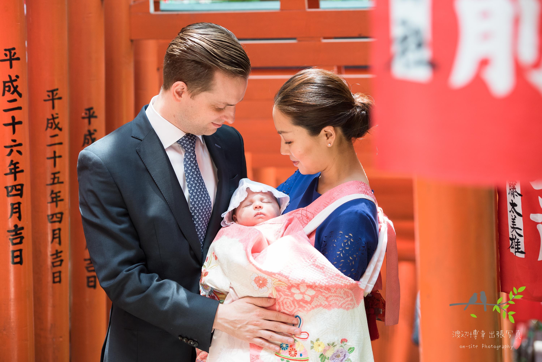赤く連続した鳥居の下で赤ちゃんを抱く掛着を着た母親と横に立つ父親