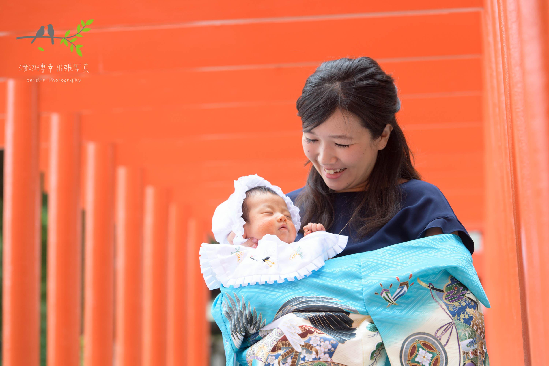 沢山の赤い鳥居ので掛着を着て立ち赤ちゃんを抱く母親