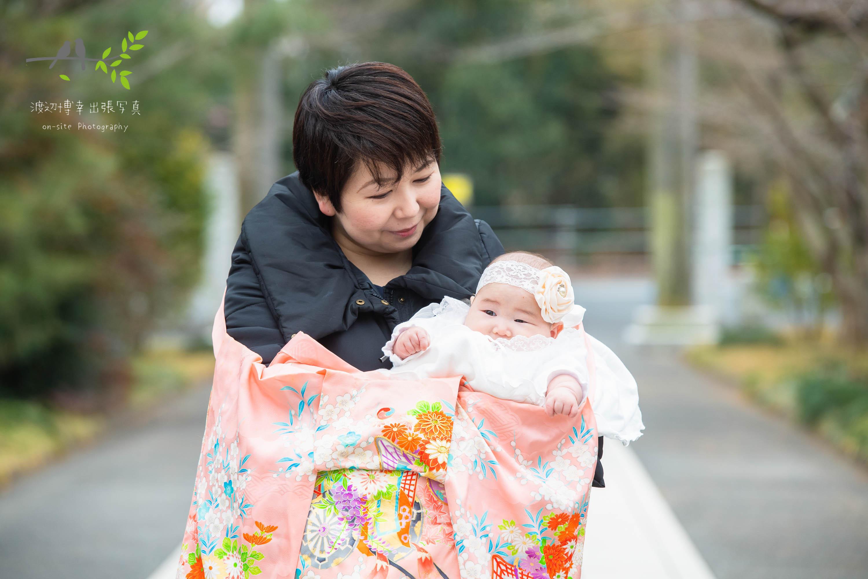 母に抱かれた掛着姿の赤ちゃん