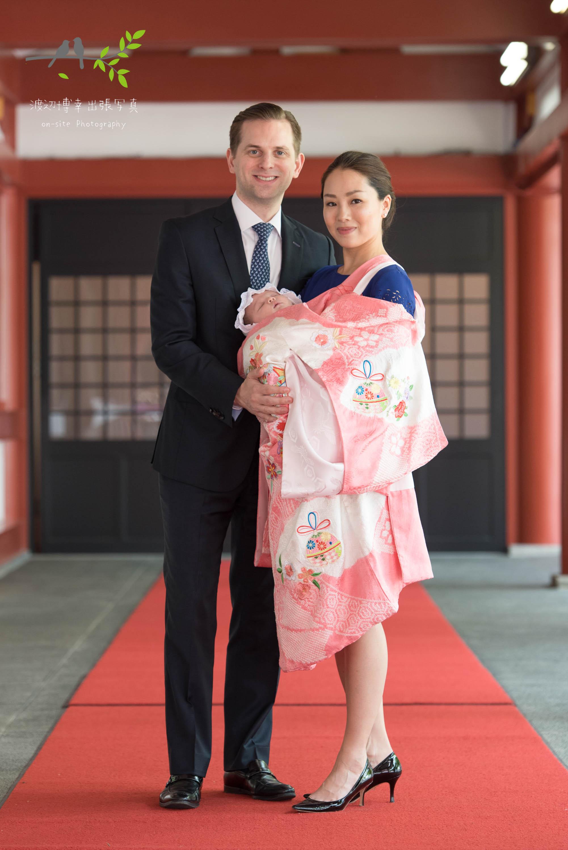 赤ちゃんを抱く掛着を着た母親と横に立つ父親
