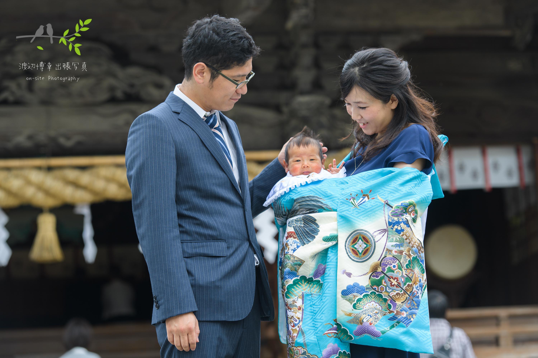 神社本殿前で掛着姿で赤ちゃんを抱く母親と横に立つ父親