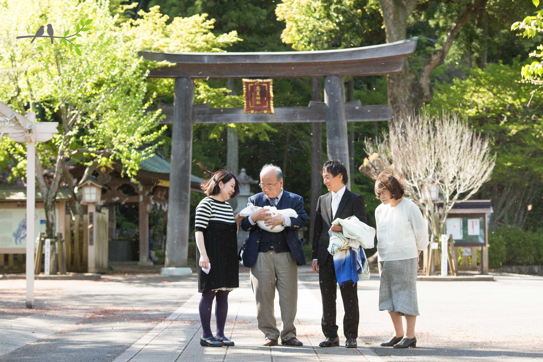 神社の鳥居の前に立つ4人家族