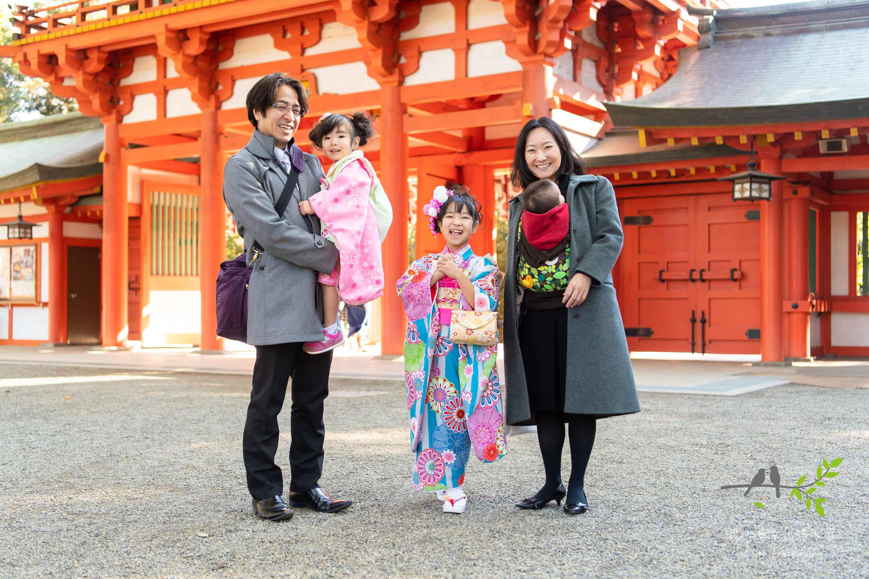 神社の赤い門のまえで記念撮影をする七五三の家族