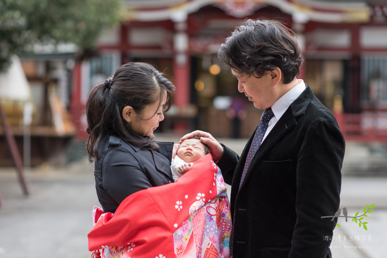 お宮参りの掛着姿で赤ちゃんを抱く母親と父親